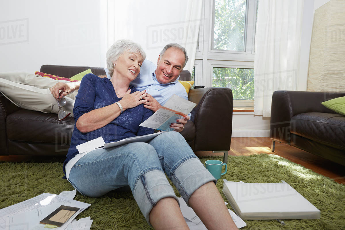 Older couple looking at photographs in living room Royalty-free stock photo