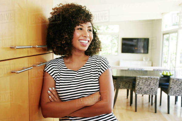 Mixed race woman leaning on cabinet Royalty-free stock photo