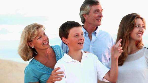 Caucasian family standing on beach, talking at sunrise Rights-managed stock video