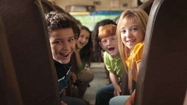 Students turn around and smile on school bus Rights-managed stock video