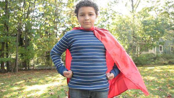 Mixed race boy in superman costume puts hands on hips Rights-managed stock video