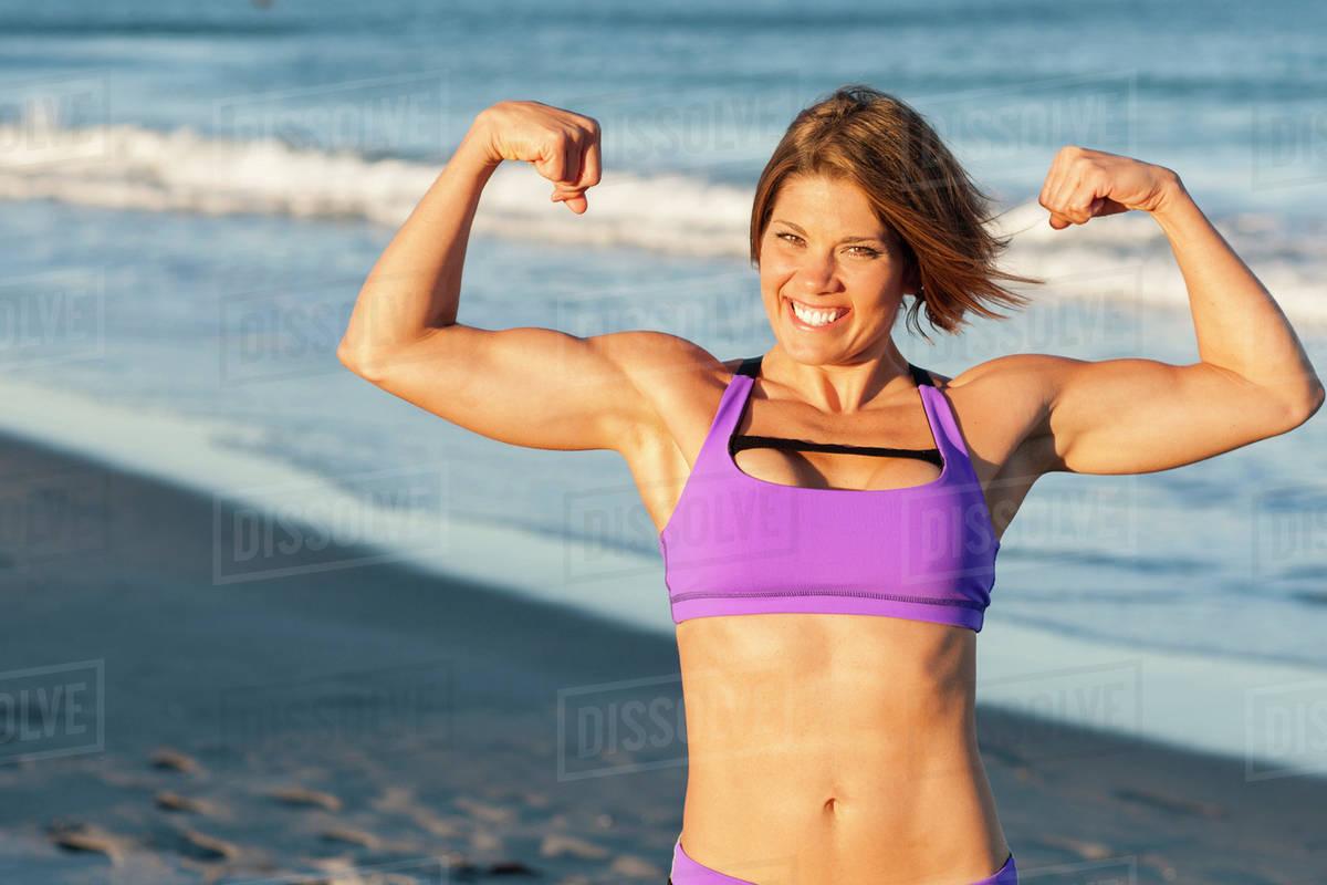 b4d3cf8be0257 Caucasian woman flexing muscles on beach - Stock Photo - Dissolve
