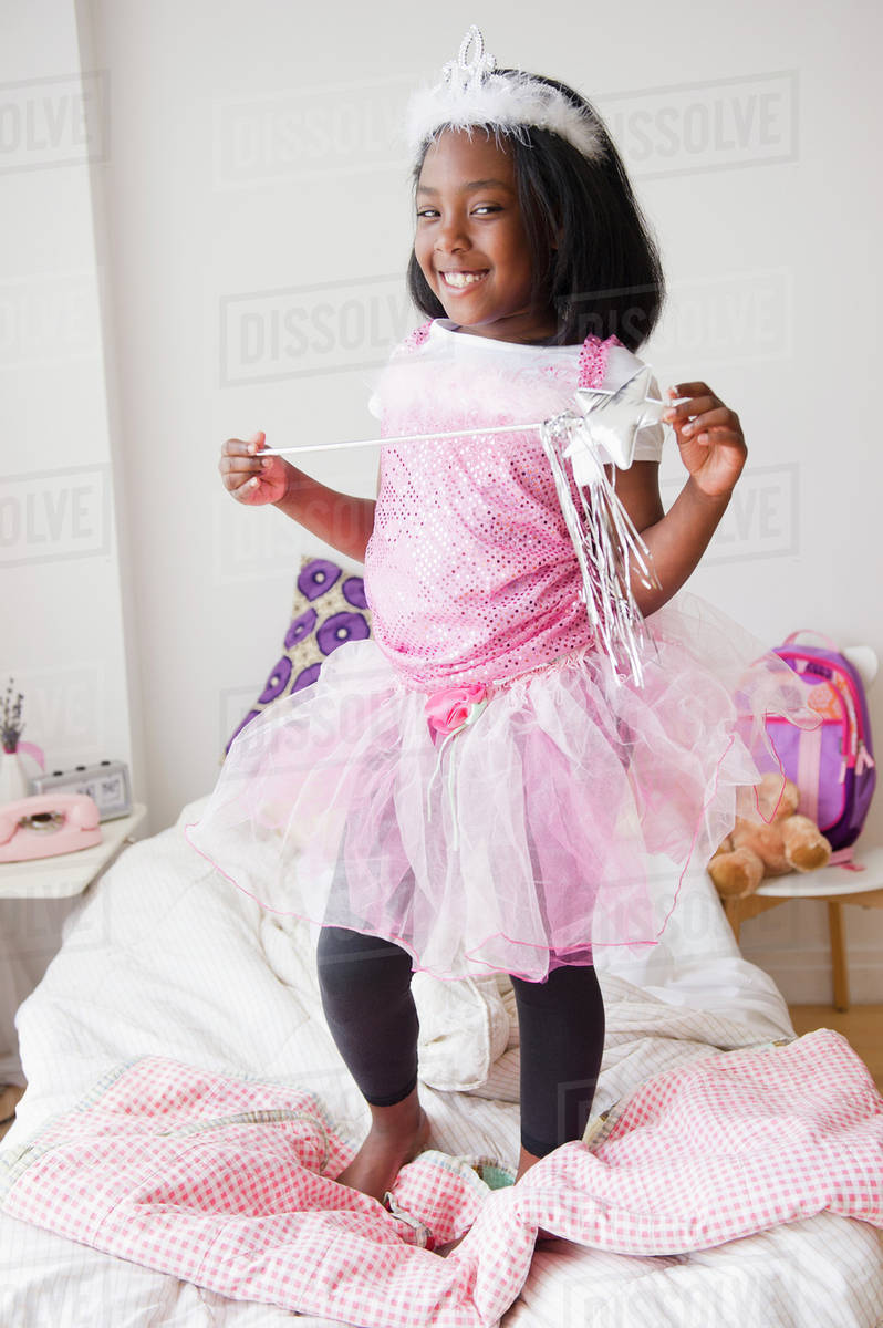 Black girl in fairy costume standing on bed Royalty-free stock photo