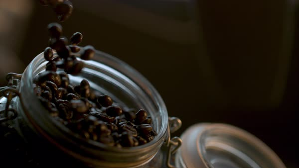Close-up shot of coffee beans falling into a jar Rights-managed stock video