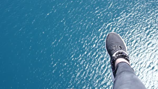 Shot begins with a close-up of feet in sneakers dangling over wavy blue water, and then tilts forward to reveal a boat with a tether leading up to where the people are parasailing Royalty-free stock video
