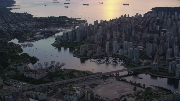 Aerial shot of modern crowded Vancouver cityscape, boats moored in inlet, British Columbia, Canada Rights-managed stock video