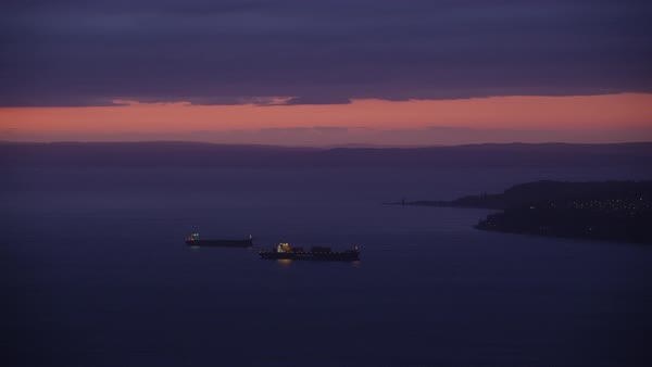 Aerial shot of boats moving in sea with crowded Seattle cityscape at sunset, Washington, United States of America Rights-managed stock video