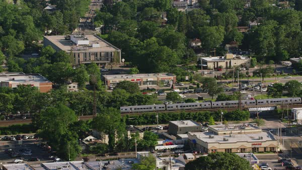 Aerial shot of a train passing through a residential area in New York Rights-managed stock video