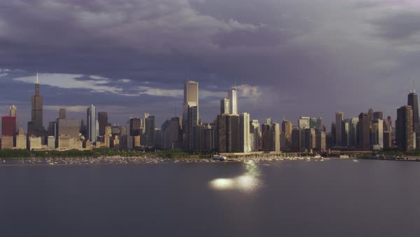 Aerial shot of skyscrapers of Chicago seen from above Lake Michigan, light reflecting on lake's surface Rights-managed stock video