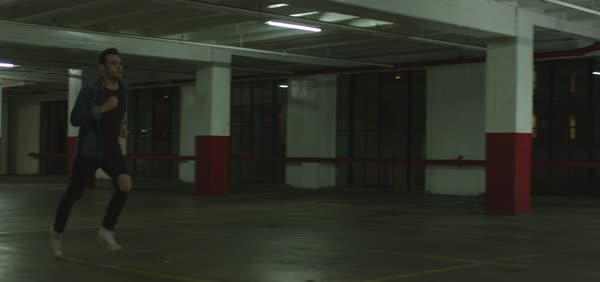 Slow motion shot of a man running in a parking garage Royalty-free stock video