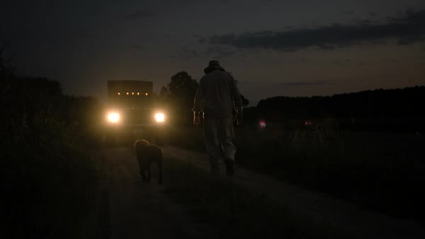 Hand-held shot of a farmer walking to his truck with his dog Royalty-free stock video