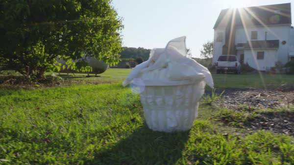 Hand-held shot of a basket of white linens in a backyard Royalty-free stock video