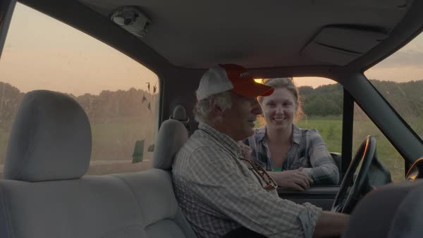 Slow motion shot of a man talking with a woman while petting his dog in a truck Royalty-free stock video
