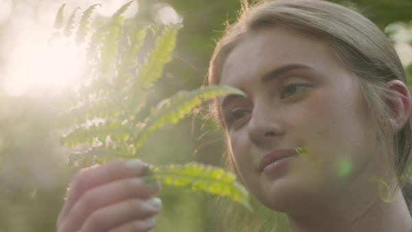 Panning shot of a young woman looking at a fern frond Royalty-free stock video