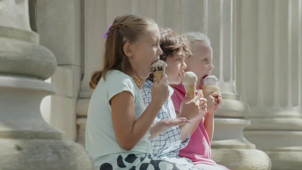 Panning shot of three children eating ice cream while sitting between two pillars Royalty-free stock video