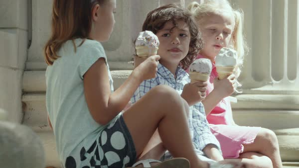 Panning shot of three children eating ice cream Royalty-free stock video