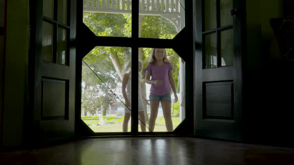 Slow motion shot of three girls opening door to come in from garden Royalty-free stock video