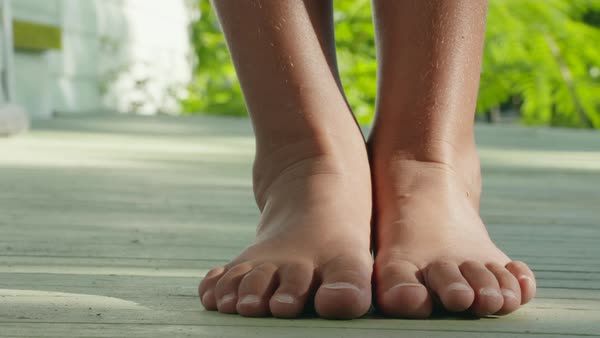 Zooming out shot of feet of a girl standing on a porch Royalty-free stock video