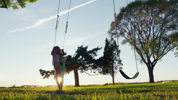Slow motion shot of a woman pushing a girl on a swing Royalty-free stock video