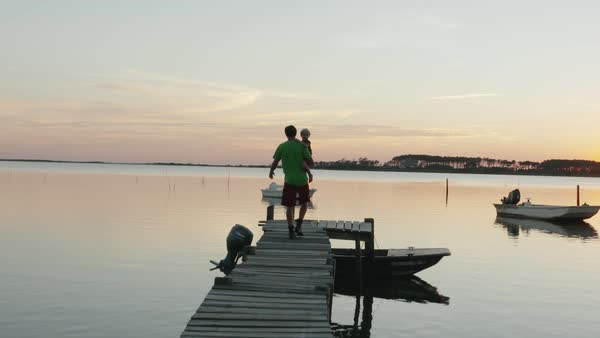 Hand-held shot of a father and his son walking and sitting down on a pier Royalty-free stock video
