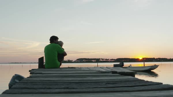 Hand-held shot of a father and sitting on a pier at sunset Royalty-free stock video
