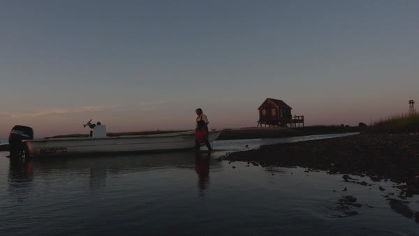 Slow motion shot of a fisherman carrying a basket of oysters to a boat Royalty-free stock video
