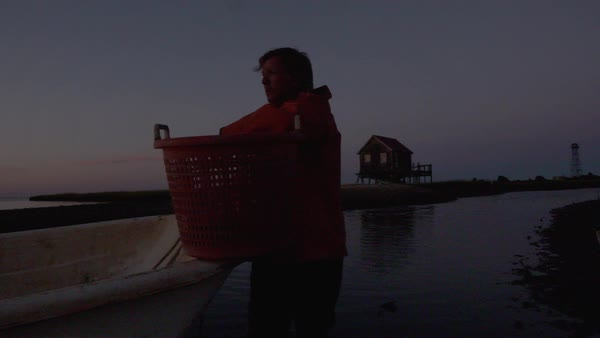 Hand-held shot of a fisherman leaning on his basket of oysters Royalty-free stock video
