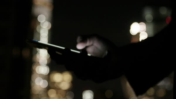 Hand-held shot of a man using his smartphone on a street in New York at night Royalty-free stock video