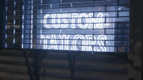 Hand-held shot of neon sign of a custom tailor Royalty-free stock video