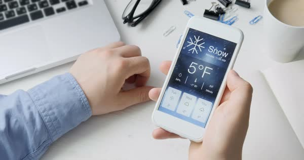 Checking weather using smartphone app, it's snowy and cold - Stock Video  Footage - Dissolve