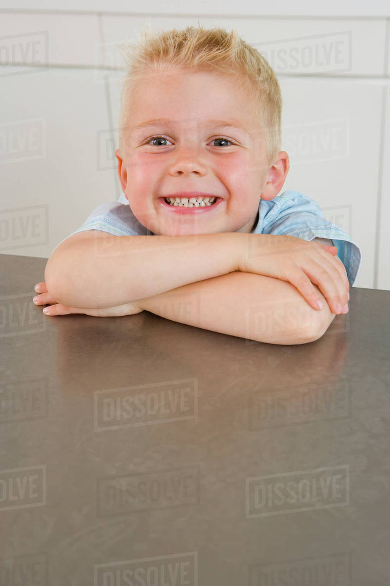boy 2 4 resting chin on arms on kitchen bench smiling - Chins Kitchen 2