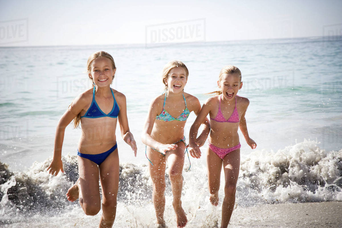 bb135c7436f9 Three young girls running out of the sea - Stock Photo - Dissolve