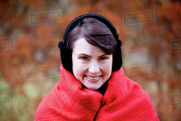 A woman wrapped up in a blanket wearing earmuffs Royalty-free stock photo