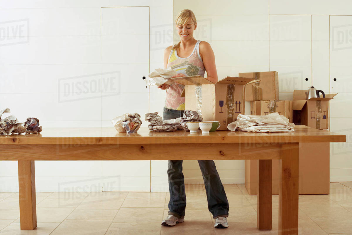 Woman Moving House Packing Crockery In Cardboard Boxes On Dining Room Table Smiling Front View