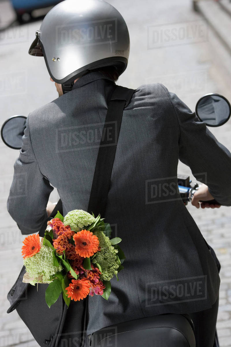 Man In Crash Helmet Riding On Scooter In Street Carrying Flower