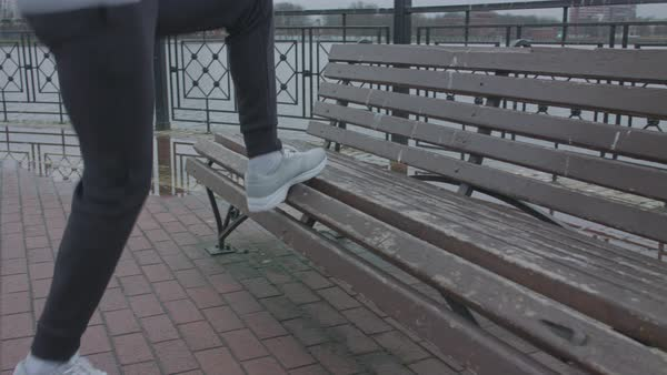 A young man running towards a bench and exercising Royalty-free stock video