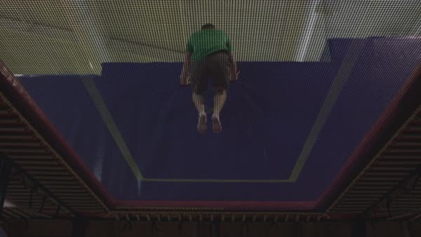 A man turning in mid-air while bouncing on a trampoline  Royalty-free stock video