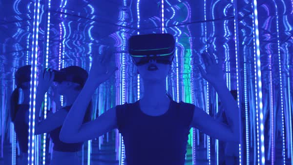 A young woman wearing VR goggles standing in a mirrored room Royalty-free stock video