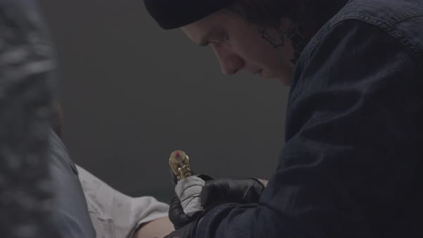 Close-up shot of a tattoo artist tattooing a man's arm Royalty-free stock video