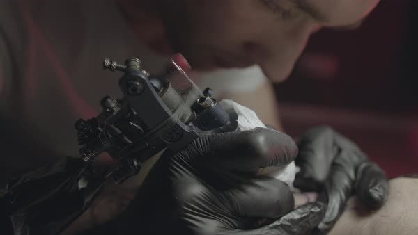 Close-up of a tattoo artist tattooing a design on a man's leg Royalty-free stock video