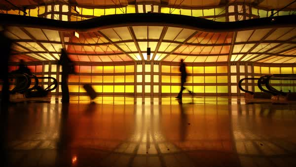 Timelapse of silhouetted people walking with suitcases between escalators Royalty-free stock video