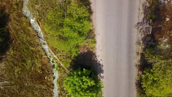 Aerial view following road and water flowing downstream next to hot spring. Royalty-free stock video