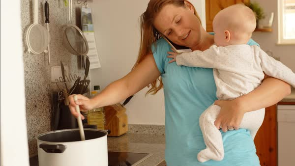 Mother holding baby while doing household chores Royalty-free stock video