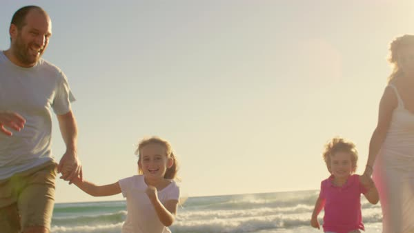 Young family running towards camera on beach Royalty-free stock video