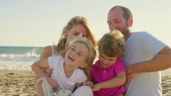 Young family sitting together on beach Royalty-free stock video