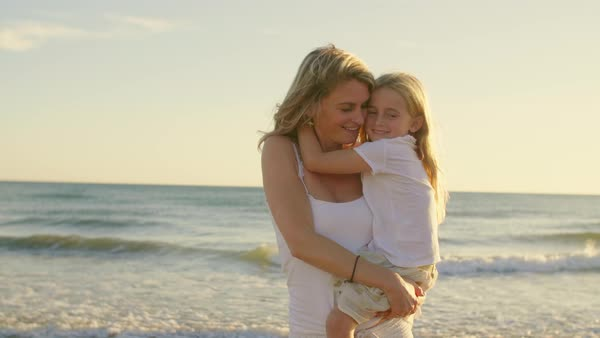 Mother and daughter standing on beach hugging and playing Royalty-free stock video
