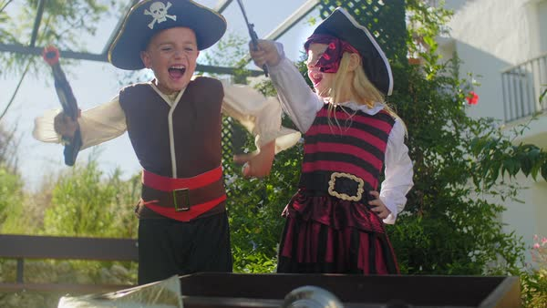 Two children in pirate costumes playing with treasure chest Royalty-free stock video