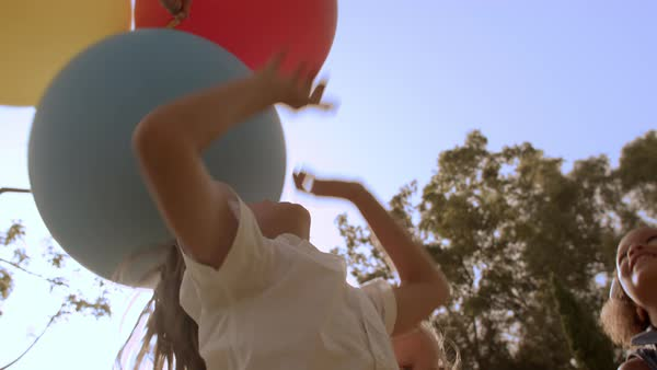 Five children jumping for balloons in park Royalty-free stock video