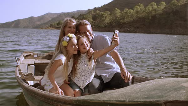 Family in rowing boat taking selfie photos on lake Royalty-free stock video