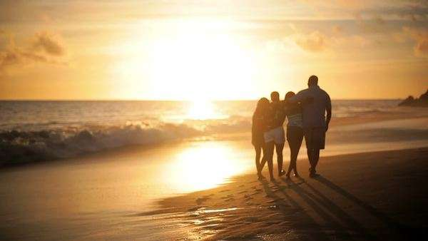 Happy family walk down the beach away from the camera Royalty-free stock video